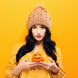 Young woman holding a pumpkin in halloween theme