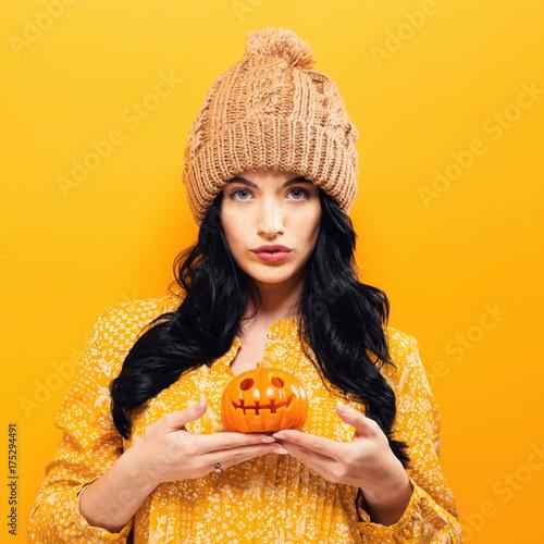 Fototapeta Young woman holding a pumpkin in halloween theme