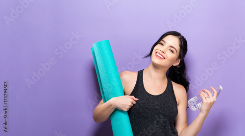 Naklejka Happy young woman holding a yoga mat