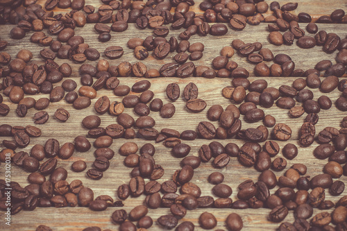 Tuinposter Brandhout textuur A lot of fragrant fresh coffee beans on a vintage style wooden table