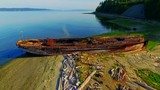 Rusty shipwreck remains of an old barge on shore of an ocean bay on a warm, bright, sunny summer morning - 175302253