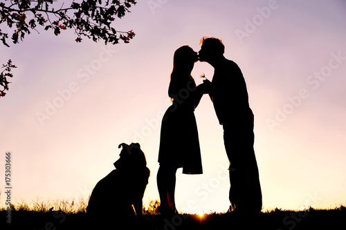 Plakat Silhouette of Loving Young Couple Kissing Under Tree at Sunset
