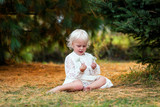 Cute Toddler Girl Sitting Outside Under Trees Exploring Nature - 175304405