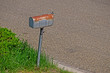 Rusty Mailbox Standing in Bright Green Grass at the Edge of a Street