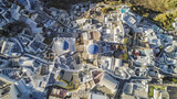 Aerial top view of white houses and blue dome church in Oia village, Santorini Island, Greece