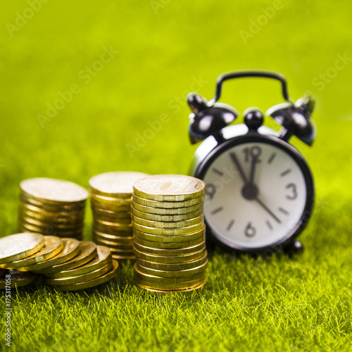 Foto op Canvas Gras Alarm clock and coins on grass.