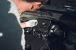 Close-up. The auto mechanic is fixing the car. Checks engine oil level