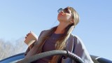 Low angle tilt down of beautiful young lady in sunglasses drinking coffee from disposal cup and smiling while filling up car at gas station at sunny day - 175320665