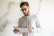 Businessman wearing glasses using tablet
