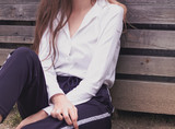 Closeup of woman wearing an elegant smart outfit with white shirt and dark trousers outdoors on wooden board background. Woman's fashion