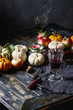 Autumn holiday table decoration setting with decorative pumpkins, apples, red leaves, glasses of red wine, candle over wooden table. Rustic style