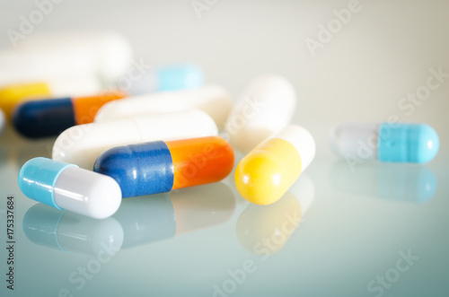 Tuinposter Apotheek Pharmacy theme. Orange, Yellow, Blue, White Isolated Capsules on the White Surface. Closeup