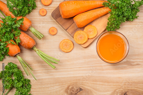 Deurstickers Sap Glass of fresh carrot juice with vegetables on wooden table.