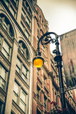 Vintage style illuminated streetlamp with New York City apartment buildings in the background. - 175341638