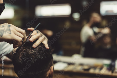 Anonymous stylish barber with tattoos cutting hair of male client in chair Poster