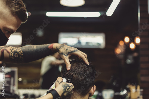 Crop tattooed stylist concentrated on shaving man with machine doing hairstyle Plakat