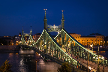 Budapest, capital of Hungary, night panorama. The illuminated Liberty Bridge on the river Danube, and University of Economics on the Pest side.