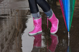 Person with pink boots and blue umbrella standing in the puddle - 175362298