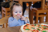 Cute funny little girl eating spaghetti in cafe - 175365813