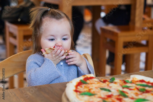 Papiers peints Pizzeria Cute funny little girl eating spaghetti in cafe