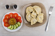 Boiled dumplings, mustard, tomato and cucumber, salt and pepper