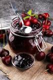 Jar of cherry jam, sour cherries and spoon on grey vintage backg
