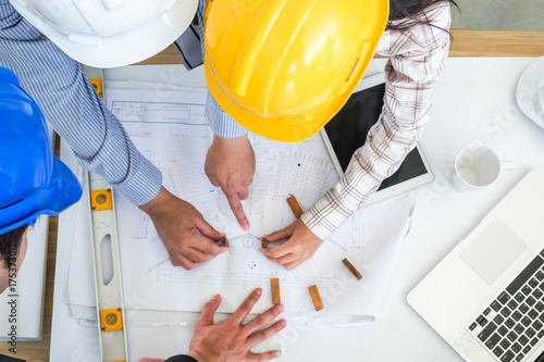 Hat engineer,Team of engineers discussing a blueprint