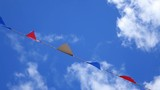 Multicolored summer Bunting flags blowing in the wind against a blue sky. - 175375295