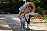 Mom teaching her son's first baby steps in the park - 175380412