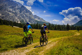 Mountain biking couple with bikes on track, Cortina d'Ampezzo, Dolomites, Italy - 175386418
