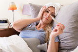 Young sick woman with fever checking her temperature with a thermometer at home - 175393618