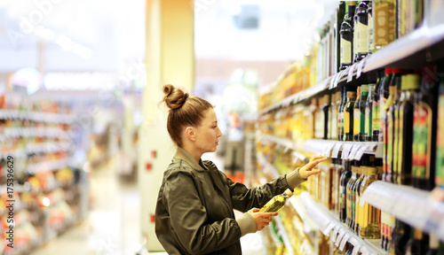 Woman shopping in supermarket reading product information.