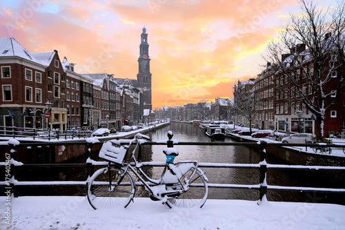 Amsterdam covered with snow with the Westerkerk in winter in the Netherlands at sunset