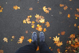 A man stands on asphalt street with colorful autumn season leaves on the floor. Point of view perspective used.