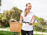 Beautiful young blonde woman with bike in park - 175418451