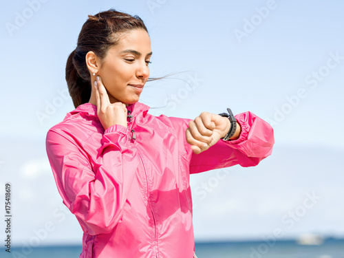 Deurstickers Jogging Young woman on beach checking heart rate after run