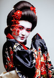 young pretty geisha in kimono with sakura and red decoration design on white background