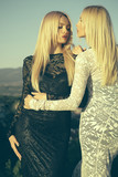 Two girls with long blond hair in lace dresses - 175436077