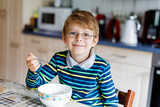 Happy little blond kid boy eating cereals for breakfast or lunch. Healthy eating for children. - 175440011