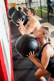 Fototapety Man And Woman Throwing Medicine Ball In Gym