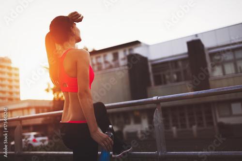 Fotobehang Fitness Beautiful female jogger doing her run in sunset