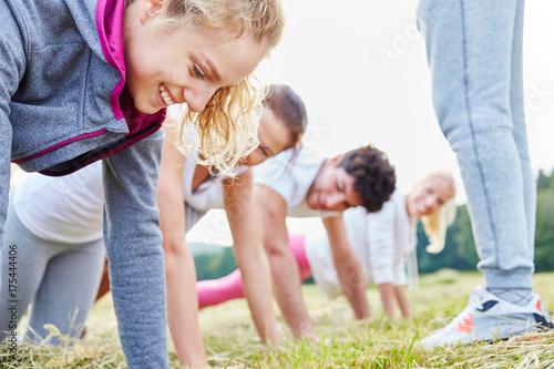 Plexiglas Fitness Gruppe junger Leute macht Liegestütz