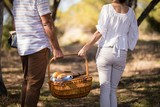 Mid-section of couple holding a wicker basket - 175447431