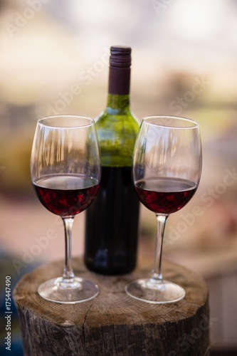 Wine bottle and glass on wooden log