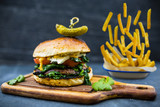 Tasty grilled vegetarian Champignon burger with spinach lettuce and blue cheese served on wooden table with copyspace, blackboard in background. - 175452431