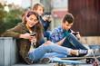 Happy smiling teens playing on smarthphones