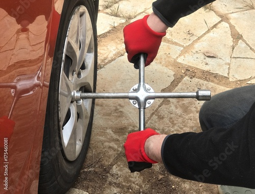 Tire fitting with cross wheel wrench. work process - 175460081