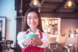 Beautiful asian barista wearing red color apron holding coffee cup and smiling at camera - 175460606