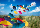 Vacation on the sea, lust for life: flying colorful umbrellas  in front of blue sky with clouds:) - 175465839