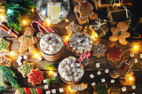 Dark wooden background with cocoa, gingerbread cookies, Christmas trees and gifts - 175468218